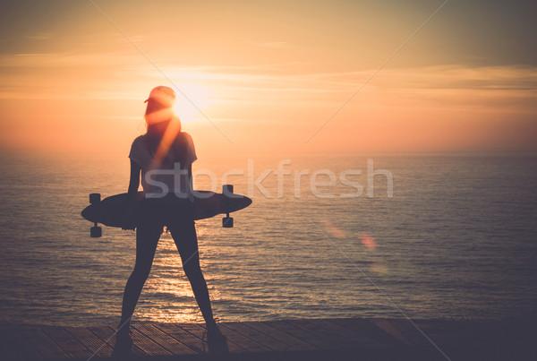 Görkorcsolyázó lány gyönyörű lány tart gördeszka naplemente Stock fotó © iko