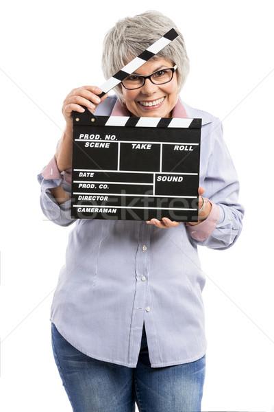 Elderly woman holding a clapboard Stock photo © iko
