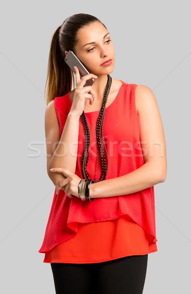 Telefoongesprek mooie vrouw geïsoleerd grijs vrouw Stockfoto © iko