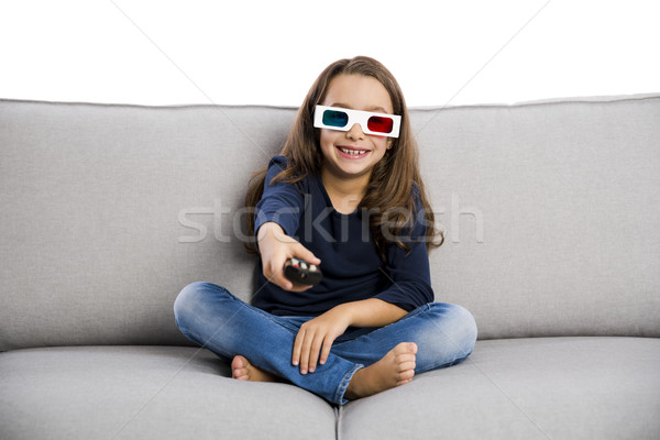 Girl holding a TV remote Stock photo © iko