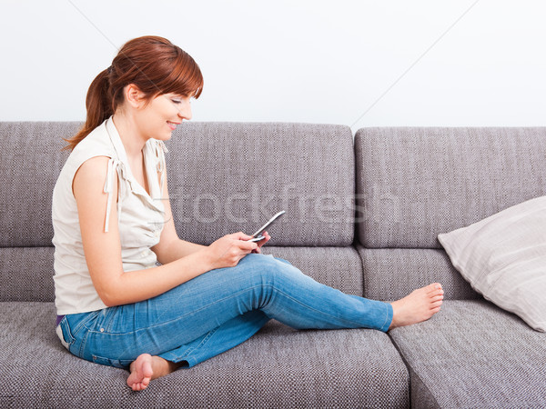 Küldés szöveges üzenet gyönyörű nő ülő kanapé tart Stock fotó © iko