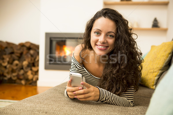 Woman with her cellphone at home Stock photo © iko