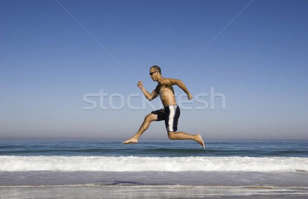 Man running and jumping on the beach Stock photo © iko
