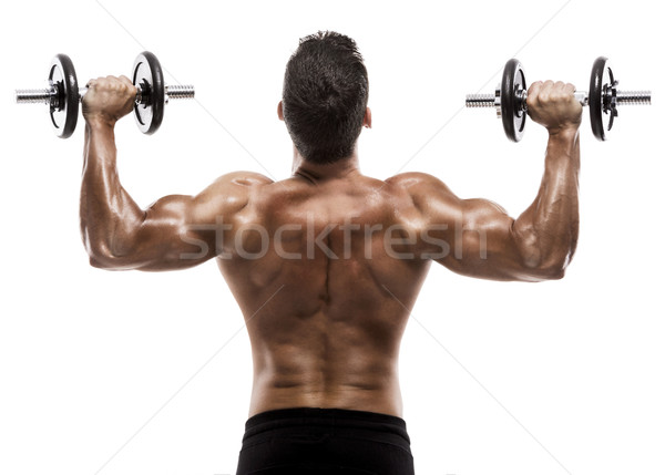 Muscle man in studio lifting weights, isolated over a white background Stock photo © iko