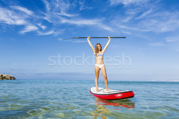 A beautiful and happy woman with arms up and learning paddle-surf Stock photo © iko