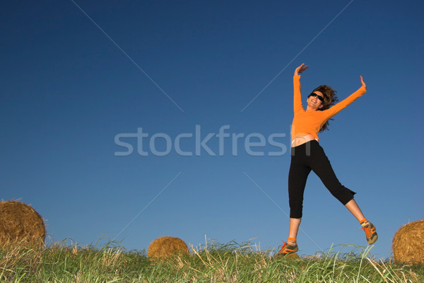 Woman jumping in a hay bales field Stock photo © iko