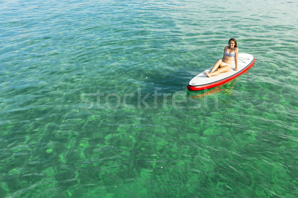 Stock photo: Woman relaxing over a paddle surfboard