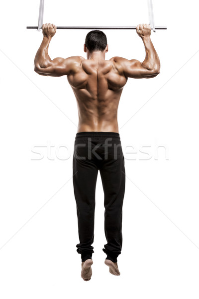 Muscle man in studio making elevations, isolated over a white background Stock photo © iko