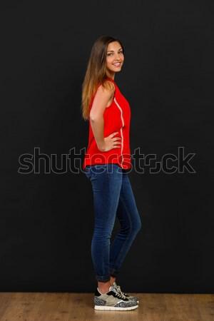 Güzel utangaç genç kadın poz siyah duvar Stok fotoğraf © iko