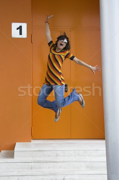 Kozmopolita lány ugrik boldogság narancs épület Stock fotó © iko