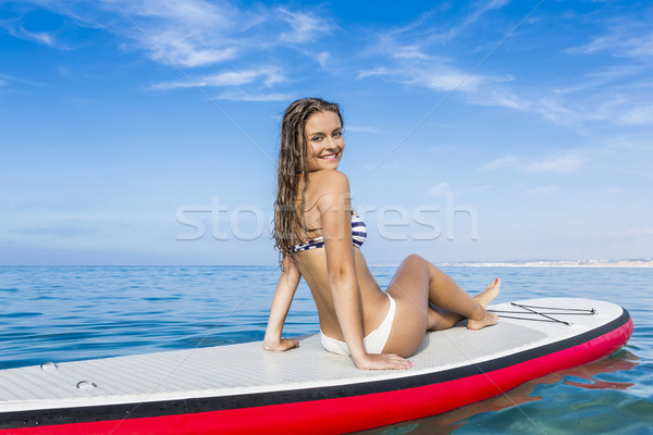 Stock photo: Woman sitting over a paddle surfboard
