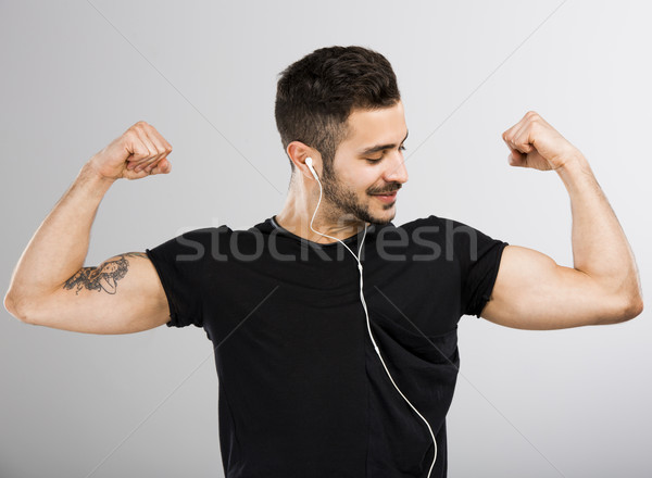 Stock photo: Man listen  music and looking his muscles