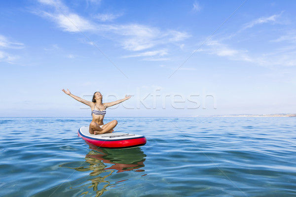 Woman relaxing over a paddle surfboard Stock photo © iko
