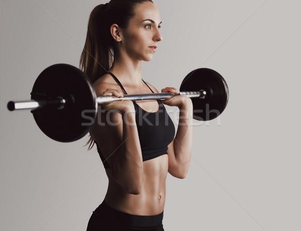 Súlyok emel lövés gyönyörű fiatal nő edzés Stock fotó © iko