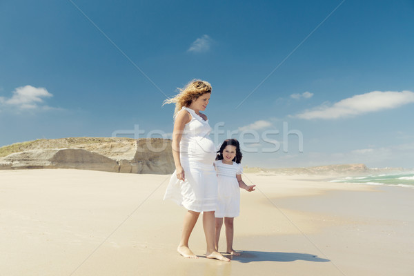 Pregnant woman and her daughter on the beach Stock photo © iko