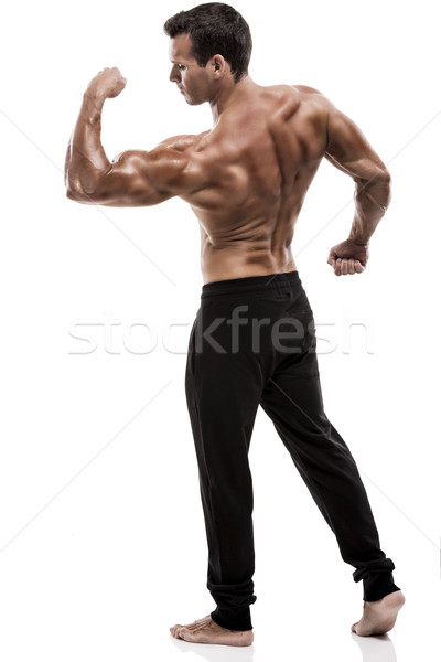Muscle man in studio and showing the biceps muscle, isolated over a white background Stock photo © iko