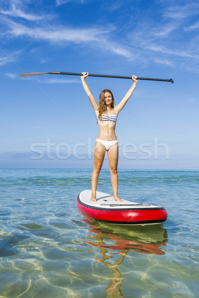 A beautiful and happy woman with arms up and learning paddle-sur Stock photo © iko