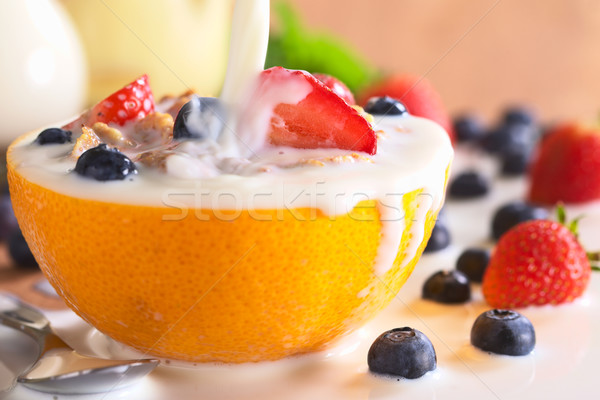 Pouring Milk Over Wholewheat Cereal with Fresh Fruits Stock photo © ildi