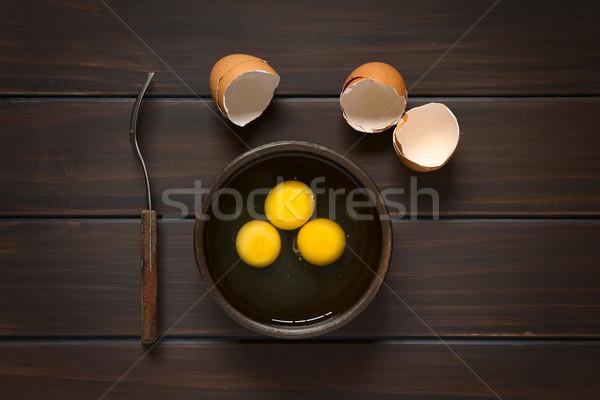 Crudo huevos tiro tres rústico tazón Foto stock © ildi