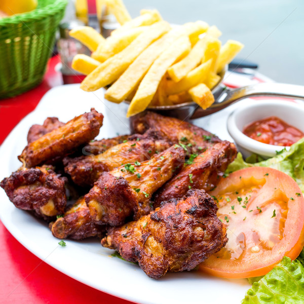 Chicken wings with sauce and golden French fries Stock photo © ilolab