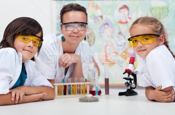 Stock photo: Teacher sitting at the desk with her young students
