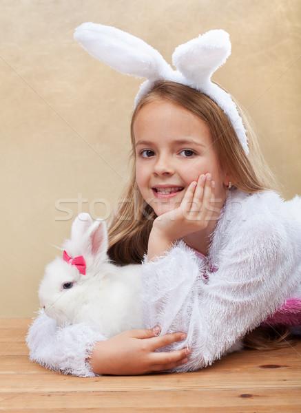 Stock photo: Little girl in bunny costume holdng her white rabbit