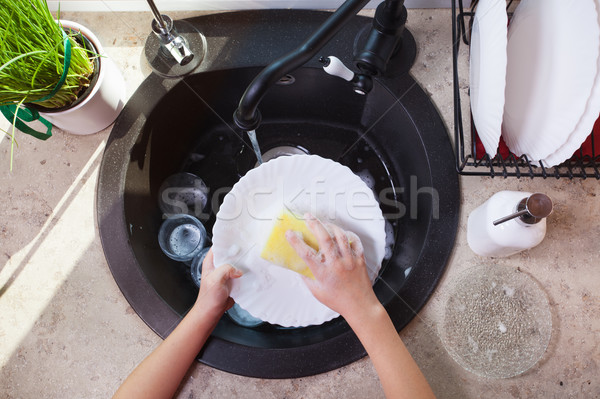 Child hands scrubbing a plate with sponge in the kitchen sink Stock photo © ilona75