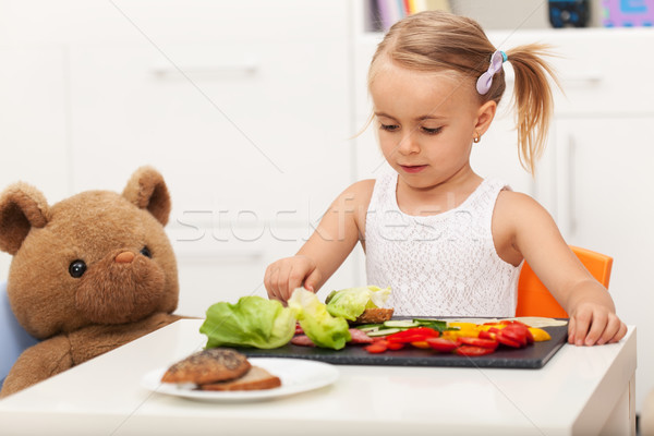 Little preschool girl having a healthy snack with her toy bear Stock photo © ilona75