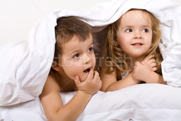 Stock photo: Kids playing under the quilt in bed