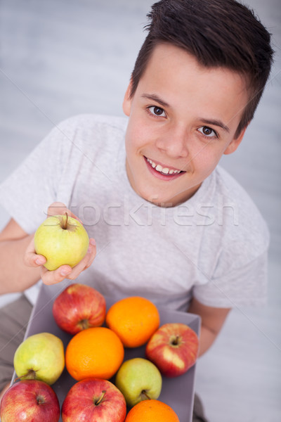Young teenager boy sitting on the floor with a plate of fresh fr Stock photo © ilona75