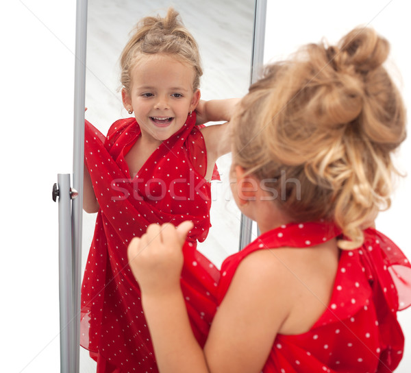 little girl trying dress in front of mirror stock photo nagy bagoly ilona ilona75 1060033. Black Bedroom Furniture Sets. Home Design Ideas