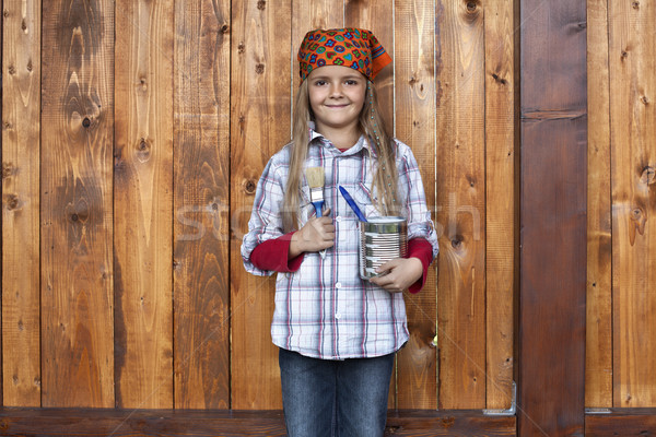Happy girl painting the wood shed Stock photo © ilona75