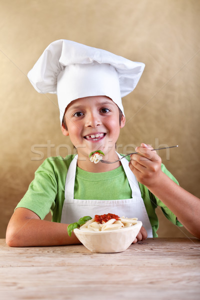 Happy boy with chef hat eating pasta Stock photo © ilona75