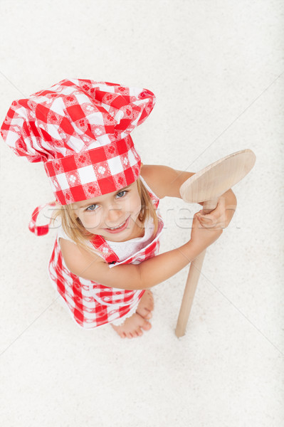 Little chef with apron and hat holding a large wooden spoon - lo Stock photo © ilona75
