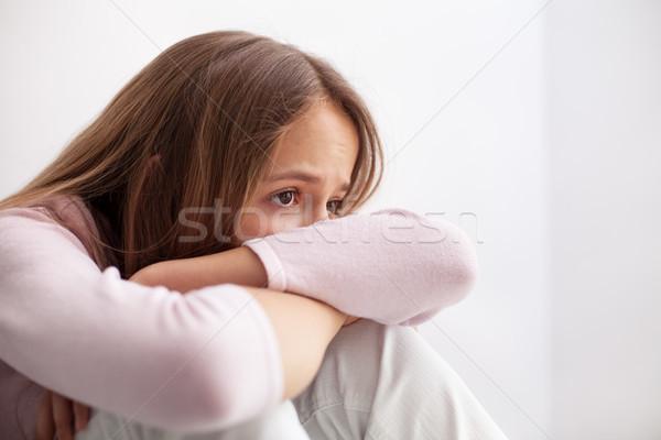Sad teenager girl sitting on the floor propping head on her knee Stock photo © ilona75
