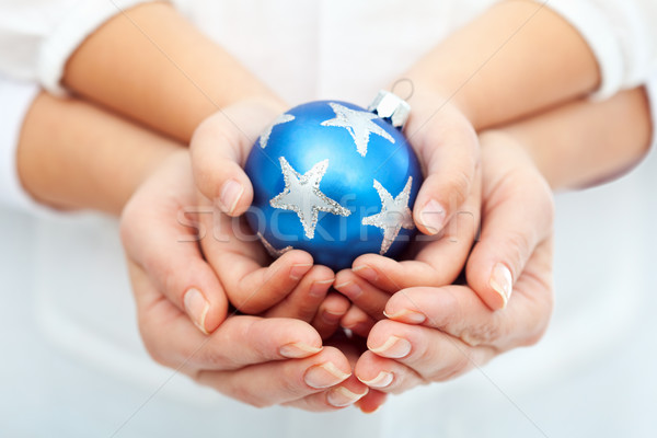Adult and child hands holding christmas bauble Stock photo © ilona75