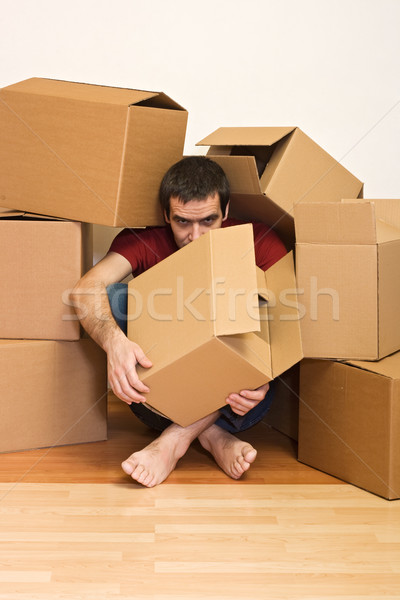 Man under cardboard boxes on the floor - moving concept Stock photo © ilona75