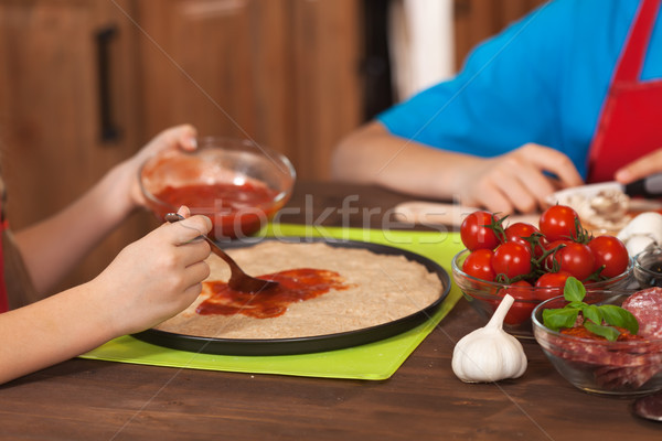 Spreading the sauce on a homemade pizza - closeup Stock photo © ilona75