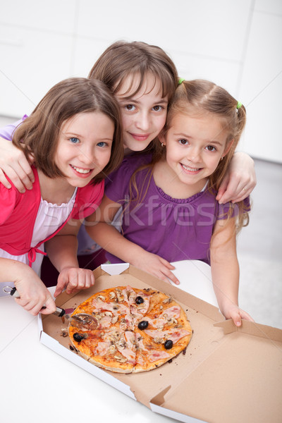 Three girlfriends sharing a pizza Stock photo © ilona75