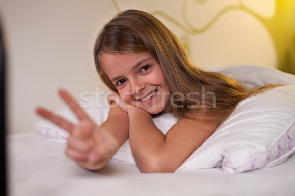 Young girl showing victory sign lying in bed, shallow depth Stock photo © ilona75