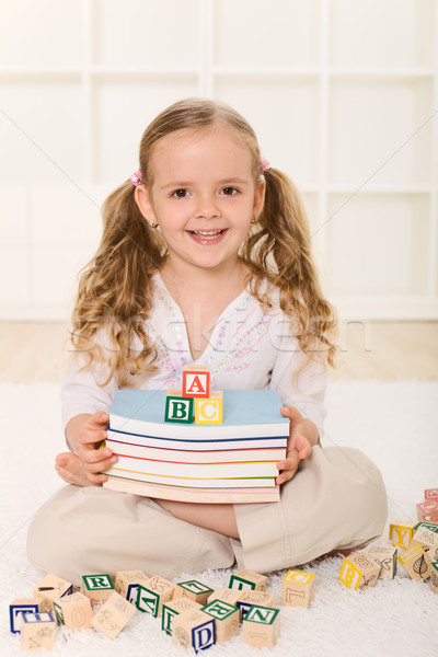 Stock photo: Little girl with books and alphabet wooden blocks