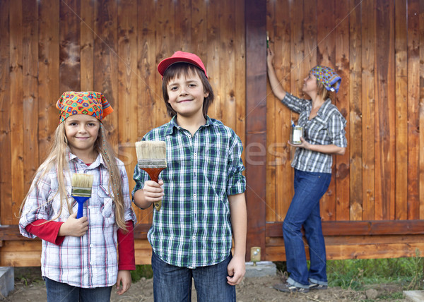 Kids helping their mother painting the wood shed Stock photo © ilona75