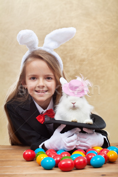 Happy magician girl holding cute bunny in magic hat Stock photo © ilona75