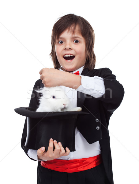 Young magician boy taking a rabbit out of his hat Stock photo © ilona75