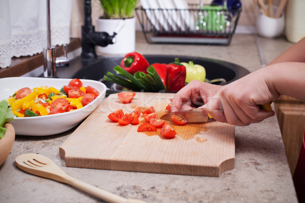 Child hands slicing cherry tomatos for a fresh vegetables salad Stock photo © ilona75