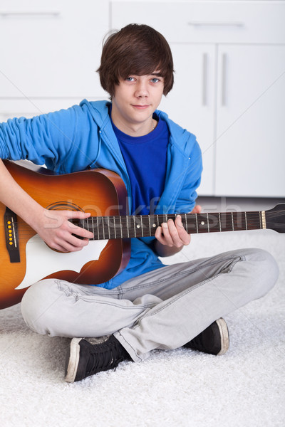 Young teenager boy playing the guitar Stock photo © ilona75