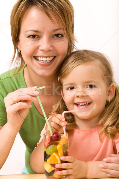 Stock photo: Woman and little girl having a fruity refreshment
