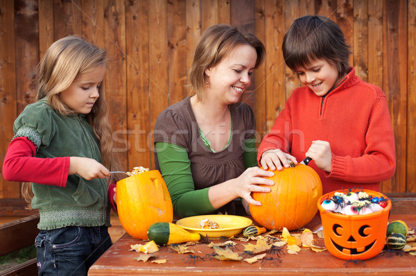 Woman helping kids to carve their Halloween jack-o-lantern Stock photo © ilona75