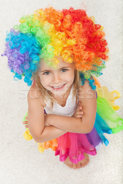 Happy little girl with colorful clown wig and a matching skirt - Stock photo © ilona75