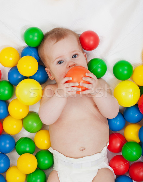 Chubby baby girl playing with colorful balls Stock photo © ilona75